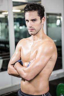 Ernstige shirtless man met armen gekruist in de sportschool