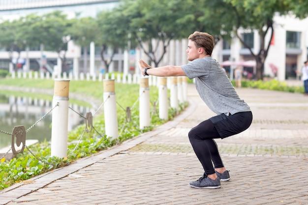 Ernstige sportieve man doing squats outdoors