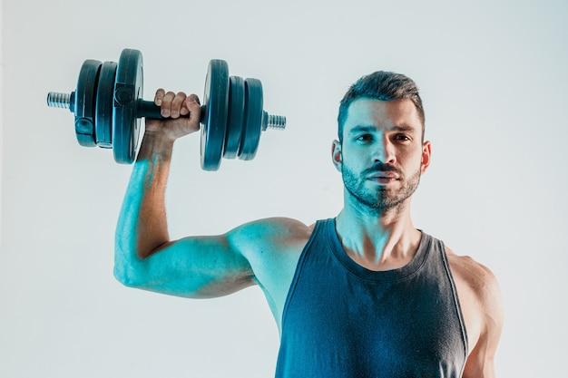 Ernstige sportman die schouderspieren traint met halter. jonge, bebaarde europese man draagt sportuniform en kijkt naar de camera. geïsoleerd op turkooizen achtergrond. studio shoot