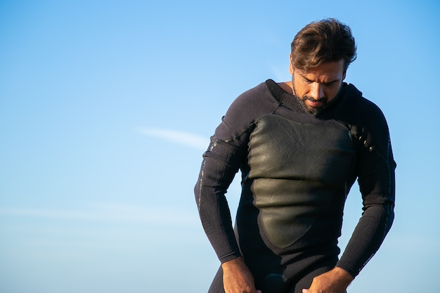 Ernstige sportman die wetsuit aantrekt om op oceaanstrand te surfen