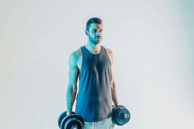 Ernstige sportman met halters. jonge, bebaarde europese man draagt sportuniform. geïsoleerd op turkooizen achtergrond. studio opname. ruimte kopiëren