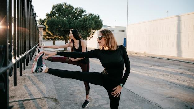 Ernstige sportvrouwen die spieren op straat uitrekken