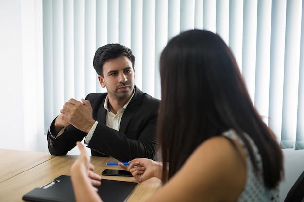Ernstige stafmedewerker die aan vrouwelijke partner of werknemer luistert