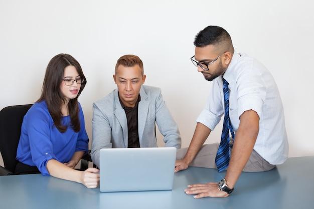 Ernstige stafmedewerkers verbindende partner via laptop