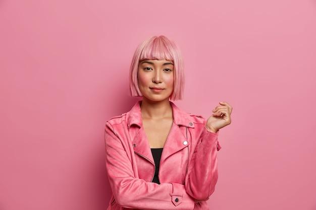 Ernstige stijlvolle dame ziet er direct kalm uit, heeft een gezonde huid, rode wangen, draagt een roze haarpruik, gekleed in een jas, houdt de hand omhoog,