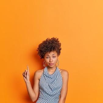Ernstige stijlvolle jonge afro-amerikaanse vrouw in modieuze polka dot kleding geeft boven op kopie ruimte aanbeveling poses geeft tegen levendige oranje achtergrond. kijk maar naar deze aanbieding