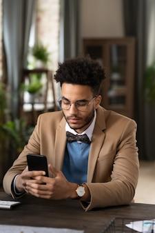 Ernstige stijlvolle jonge zakenman van gemengd ras met afro-kapsel met een bril en een vlinderdas die aan het bureau zit en de telefoon controleert