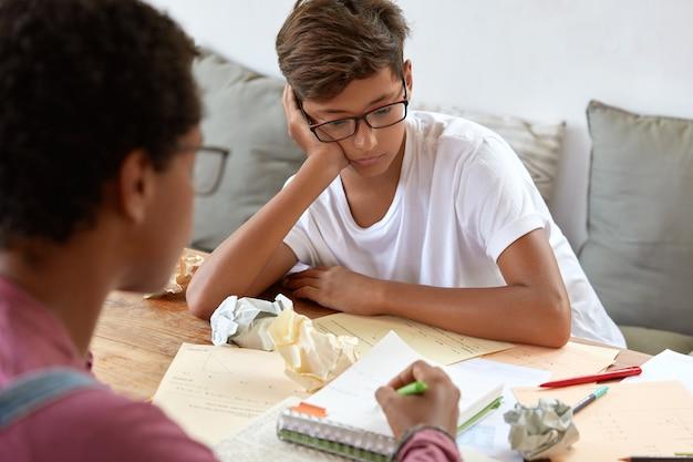 Ernstige stijlvolle jongen met bril probeert te begrijpen hoe taak in meetkunde te maken