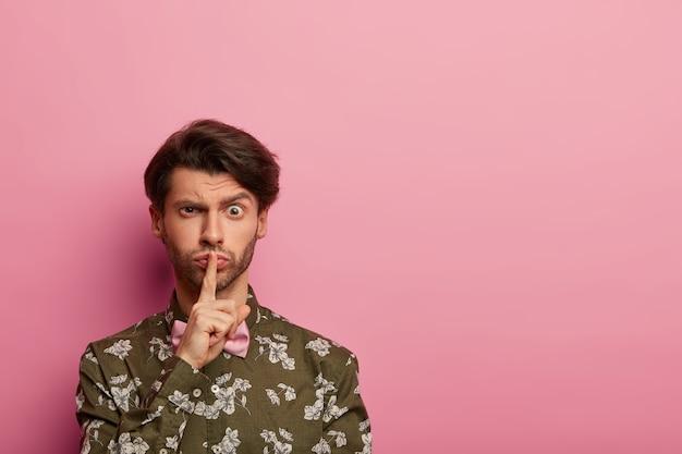 Ernstige stijlvolle man maakt stilte, roddelt of vertelt geheim, houdt wijsvinger over lippen, vraagt om stil te zijn, draagt shirt met bloemenprint