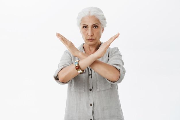 Ernstige strenge grootmoeder toont een dwarse gebaar, verbiedt of keurt actie af