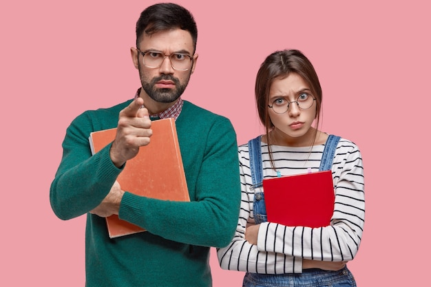 Ernstige strenge mannelijke professor houdt dik leerboek vast, wijst rechtstreeks naar je, mooie assistent met ronde bril staat dichtbij