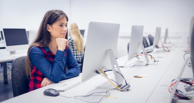 Ernstige student die aan computer bij universiteit werkt