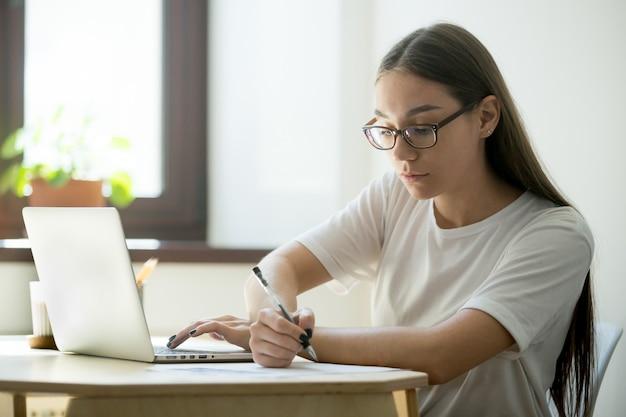 Ernstige student die bij laptop werkt die voor examens voorbereidingen treft