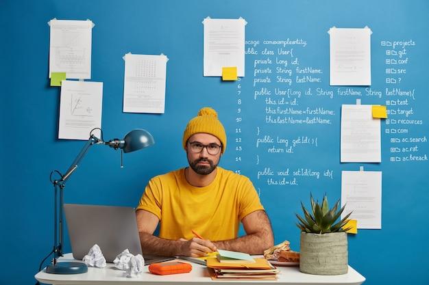 Ernstige student gaat naar trainingswebinar kijken, werkt aan cursusplan, maakt artikel in kladblok, draagt gele hoed, t-shirt en bril