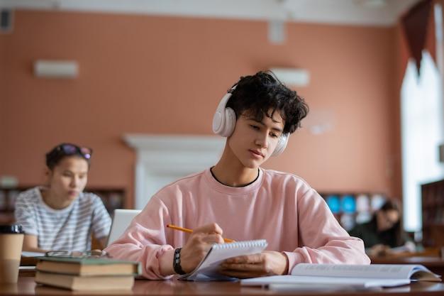 Ernstige student in hoofdtelefoons en vrijetijdskleding die na de lessen in bibliotheek zitten en voor seminarie voorbereiden