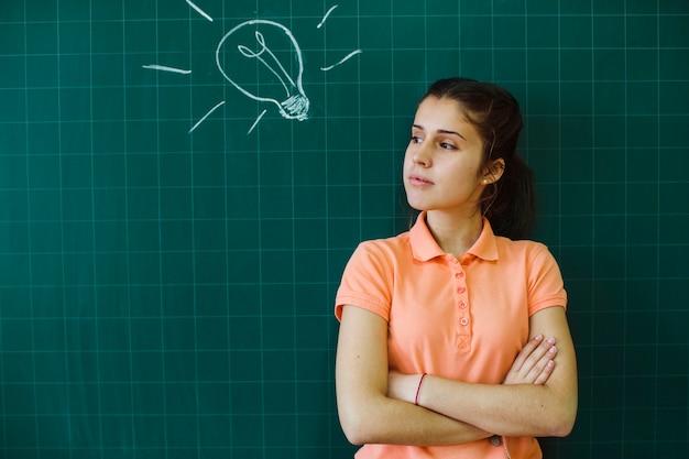 Ernstige student poseren voor het schoolbord