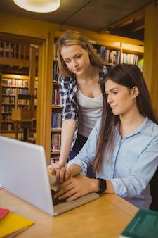 Ernstige studenten die laptop in bibliotheek met behulp van