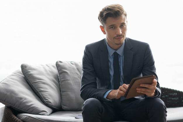 Ernstige succesvolle jonge man met behulp computer van de tablet