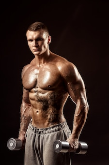 Ernstige tattoed shirtless atleet opheffing van metalen halters training op donkere muur