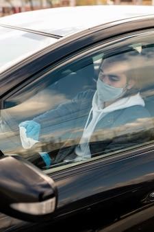 Ernstige taxichauffeur in doek masker zit in auto en stuurwiel met servet desinfecteren