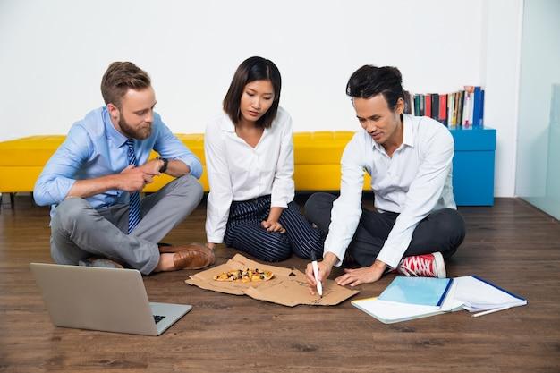 Ernstige team bespreken strategie voor pizzadoos