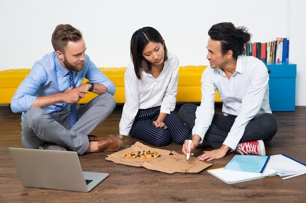 Ernstige team eten van pizza en met discussie