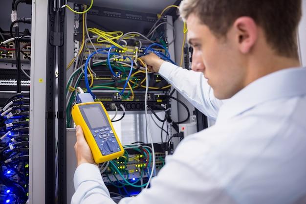 Ernstige technicus die digitale kabelanalysator op server gebruikt