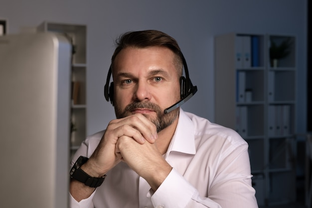 Ernstige telefoniste met hoofdtelefoon op zoek naar jou zittend achter computerscherm op kantoor