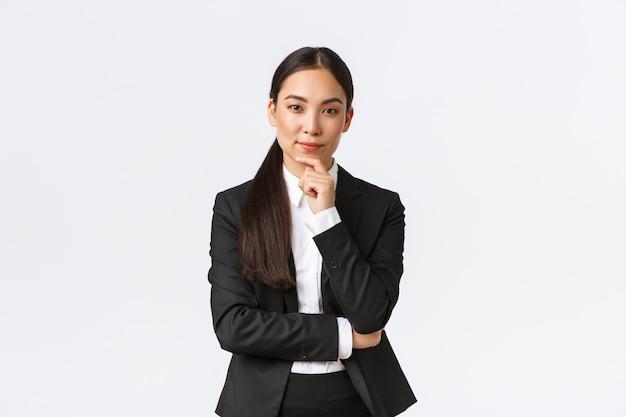 Ernstige tevreden aziatische zakenvrouw heeft een interessant idee, raakt de kin aan en kijkt sluw naar de camera, staat attent, denkt terwijl hij in pak staat op een witte achtergrond