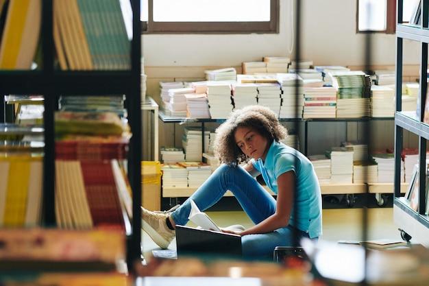 Ernstige tienermeisje artikelen in verschillende boeken lezen bij het maken van project op laptop voor wetenschapsklas