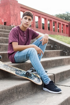 Ernstige tienerzitting op trappen met skateboard weg kijkend