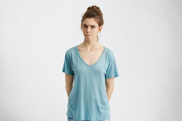 Ernstige twijfelachtige, niet-overtuigde jonge vrouw kleedde zich nonchalant op de lippen, met een besluiteloze, verwarde uitdrukking op het gezicht, wantrouwend en onzeker kijkend tijdens ruzie.