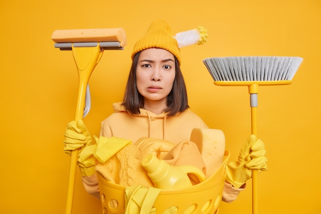 Ernstige verbaasde huisvrouw weet niet waar ze moet beginnen met schoonmaken gekleed in vrijetijdskleding gebruikt dweil en bezem voor het wassen van de vloer, de was houdt het huis schoon. huishoudelijke klusjes concept