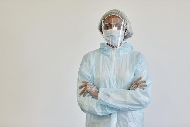 Ernstige verpleegster in pbm-pak medisch masker en handschoenen die de armen kruisen en naar de camera kijken die van wit is geïsoleerd