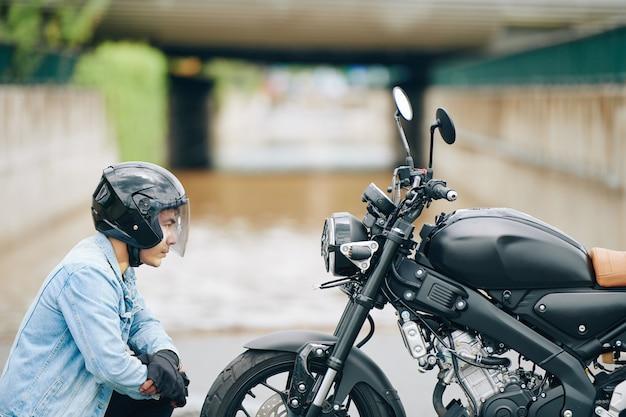Ernstige vietnamese fietser die in helm koplamp van motorfiets bekijkt