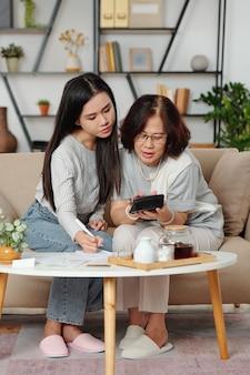 Ernstige vietnamese moeder en volwassen dochter die rekeningen en andere uitgaven berekenen