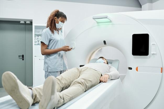 Ernstige volwassen arts in laboratoriumjas wijzend op röntgenfoto tijdens het bespreken van de resultaten met verpleegkundige in de kamer van de patiënt