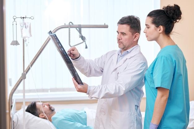 Ernstige volwassen arts in laboratoriumjas wijzend op x-ray beeld tijdens het bespreken van resultaten met verpleegkundige in patiënten kamer