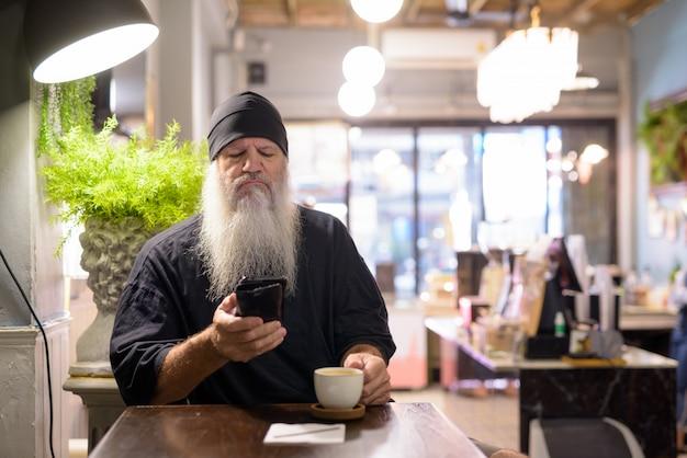 Ernstige volwassen bebaarde hipster man met behulp van telefoon in de coffeeshop