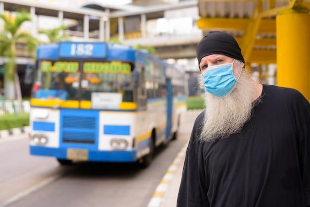 Ernstige volwassen bebaarde hipster man met masker tijdens het wachten bij de bushalte