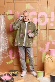 Ernstige volwassen bebaarde man draagt vuile kleren na het schilderen van muren van huis renoveert kamer houdt penseel kijkt zelfverzekerd naar de camera. herstel gebouw en huis make-over. mannelijke schilder of bouwer