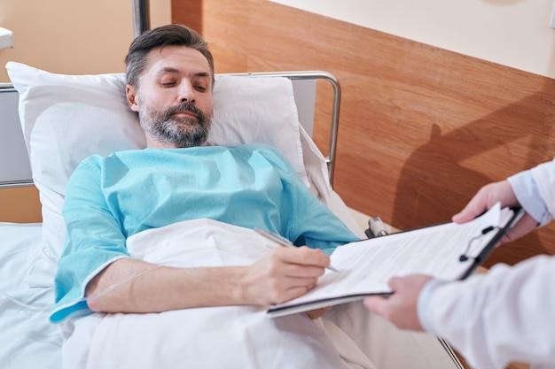 Ernstige volwassen bebaarde man in ziekenhuisbed medische overeenkomst ondertekenen vóór chirurgische ingreep