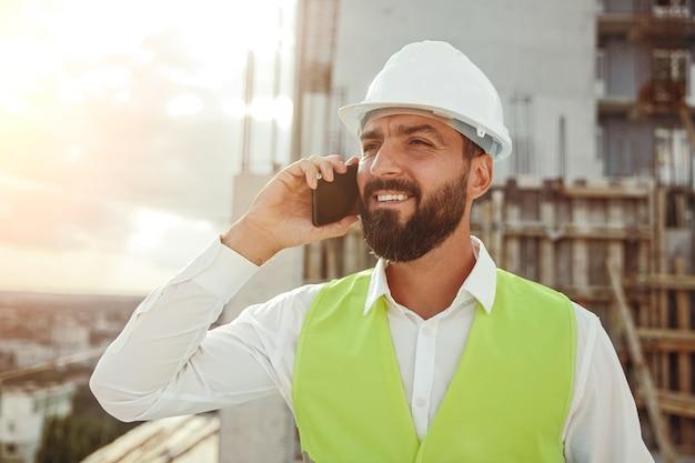 Ernstige volwassen bebaarde mannelijke ingenieur in veiligheidshelm en vest praten op mobiele telefoon en bestelling maken voor project terwijl u werkt op de bouwplaats