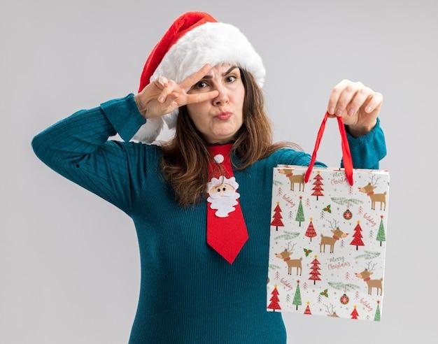 Ernstige volwassen blanke vrouw met kerstmuts en kerststropdas houdt papieren geschenkdoos en gebaren overwinningsteken geïsoleerd op een witte muur met kopieerruimte