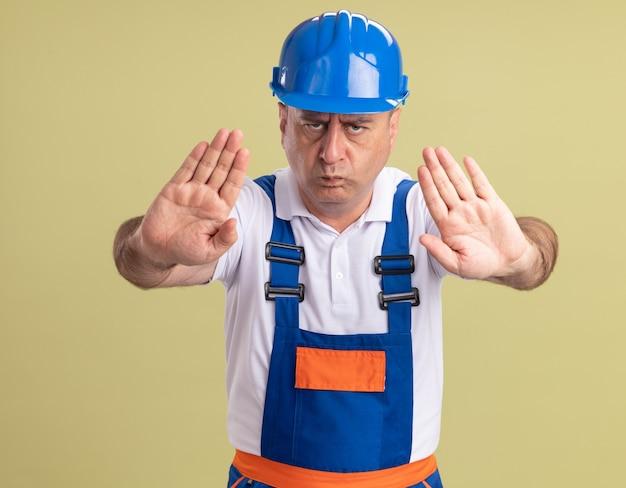 Ernstige volwassen bouwer man in uniforme gebaren stop handteken met twee handen geïsoleerd op olijfgroene muur