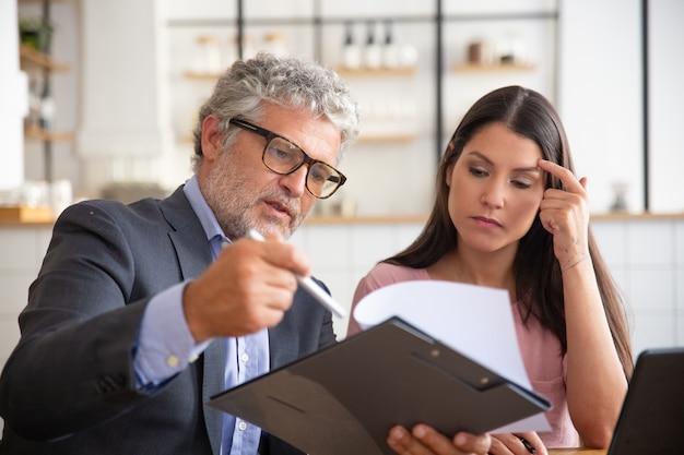 Ernstige volwassen juridisch adviseur die document leest, analyseert en uitlegt aan vrouwelijke klant