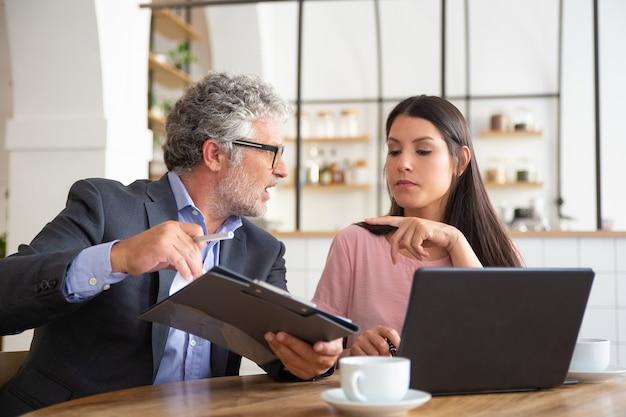 Ernstige volwassen juridische deskundige die document leest, analyseert en uitlegt aan vrouwelijke klant
