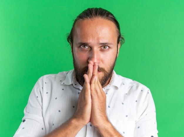 Ernstige volwassen knappe man die de handen bij elkaar houdt en de mond aanraakt terwijl hij naar de camera kijkt die op de groene muur is geïsoleerd Premium Foto