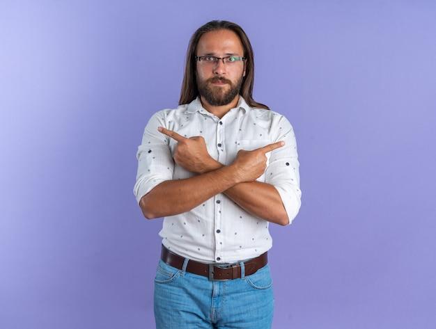 Ernstige volwassen knappe man met een bril die de handen gekruist houdt en naar de zijkanten kijkt en naar de camera kijkt die op een paarse muur met kopieerruimte is geïsoleerd