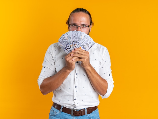 Ernstige volwassen knappe man met een bril die geld vasthoudt en naar de camera kijkt van erachter geïsoleerd op een oranje muur